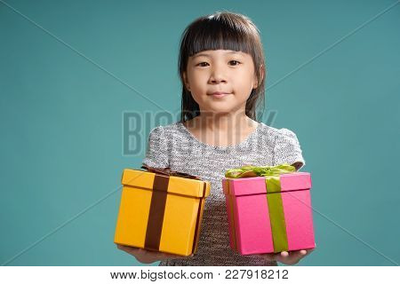 Portrait Of Little Asian Girls Holding Two Birthday Presents ,  Isolated On Light Green Background .
