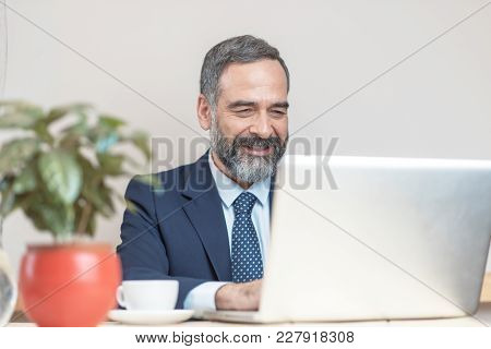 Senior Old Business Man Using His Cell Computer In A Coffee Shop During A Work Break