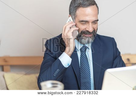 Senior Old Business Man Using His Cell Phone In A Coffee Shop During A Work Break