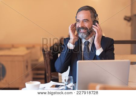 Senior Old Business Man Listening To His Favorite Music Through A Pair Of Big Headphones In A Coffee