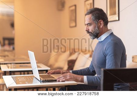 Senior Retired Man Sitting In A Coffee Shop And Using His Laptop
