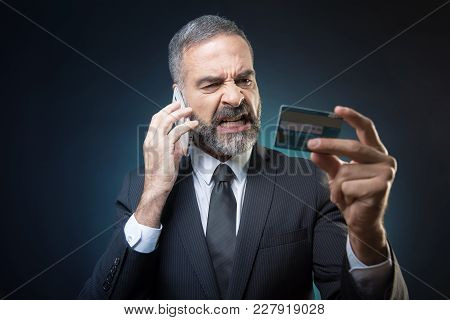 Furious And Enraged Senior Business Man Fighting With Bank Clerk Over His Account Or Credit Card Bal