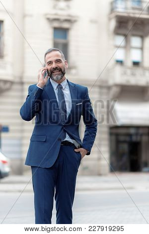 Casual Senior Business Man Walking The Street And Talking On His Cell Phone, Urban Outdoor Area