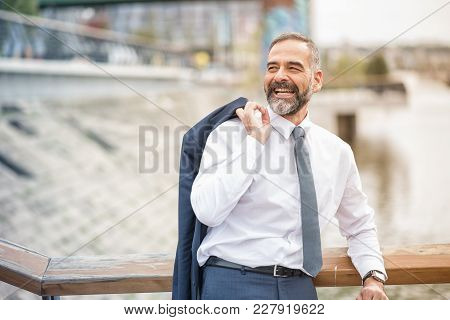 Confident Senior Business Man Taking A Break From Work, Enjoying A Nice Day Outside