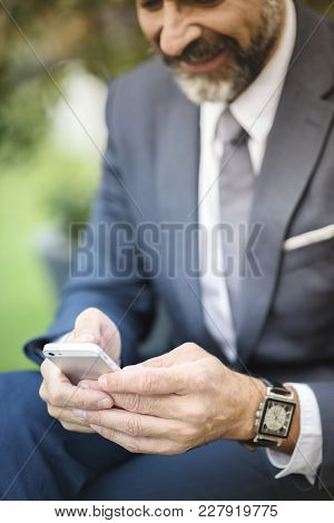 Senior Business Man Typing A Text Message On His Cellphone, Sitting On A Bench In A Park Closeup