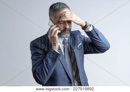 Worried Senior Business Man Has A Very Stressful Conversation On His Cell Phone