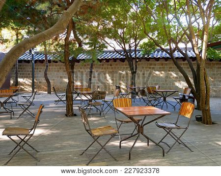 Korean Outdoor Cafe. Empty Tables And Chairs Outside A Traditional Stone Wall In Seoul, South Korea.
