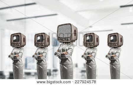 Business Women In Suits With Old Tv Instead Of Their Heads Keeping Arms Crossed While Standing In A