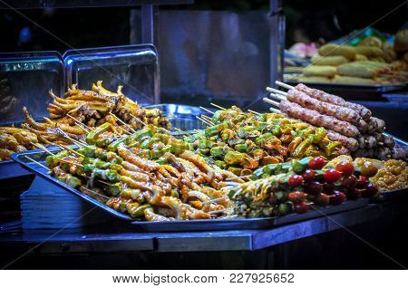 Street Foods At Night Market In Asia With Varieties Of Meats To Choose