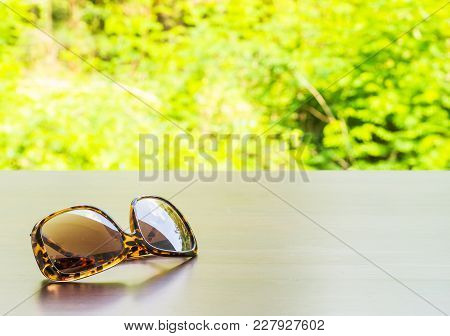 Brown Fashion Sun Glasses On Wooden Brown Table Outside Room Inside Big Forest