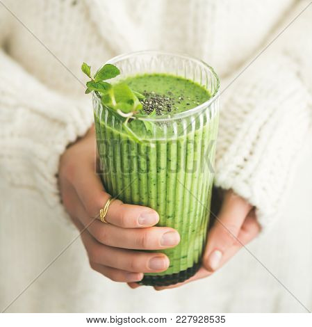 Matcha Green Vegan Smoothie With Chia Seeds And Mint In Glass In Hands Of Female Wearing White Sweat