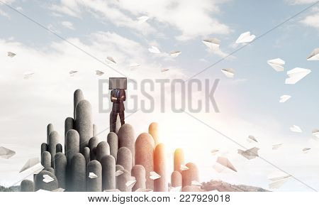 Businessman In Suit With Tv Instead Of Head Keeping Arms Crossed While Standing On The Top Of Stone