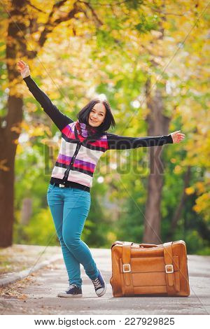 Young Teen Girt With Suitcase In A Park