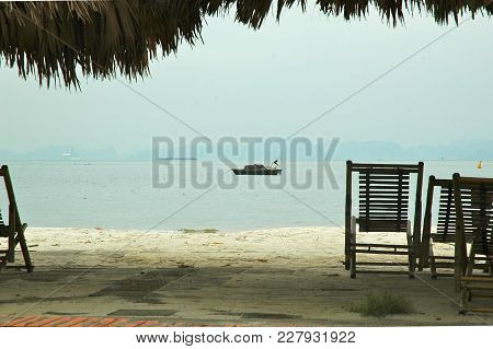 Wooden Chairs Are On A Path Overlooking Halong Bay, Vietnam. An Old Fishing Boat Is Moored In The Wa