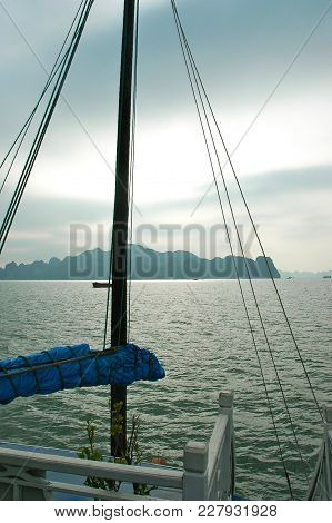 The Bare Mast And Ropes Of A Boat Frame The View Over The Islands And Rocks Of Halong Bay In Vietnam