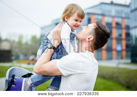 A Young Dad Sits A Small Daughter In A Chair Before Riding A Bicycle.