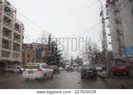 Rain On The City Street Through A Car Windshield. Rain Drops On Window, Rainy Weather. Inside Car Wh