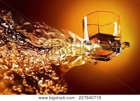 Glass Of Whiskey With Ice. View From The Bottom . Conceptual Image With Abstract Splashing . Copy Sp