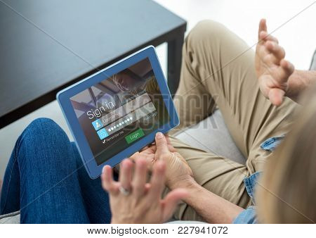 Digital composite of Couple with tablet on the sofa. Screen with login
