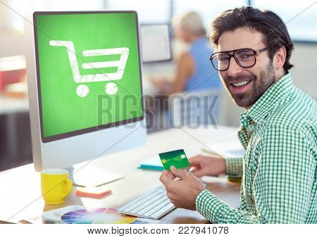 Digital composite of Man using computer with Shopping trolley icon
