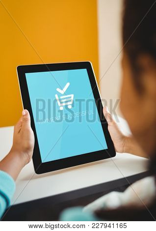 Digital composite of Woman using Tablet with Shopping trolley icon
