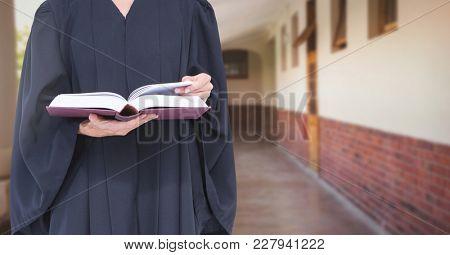Digital composite of Judge holding book in front of corridor