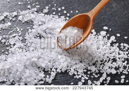 spoon of coarse grained sea salt on black background
