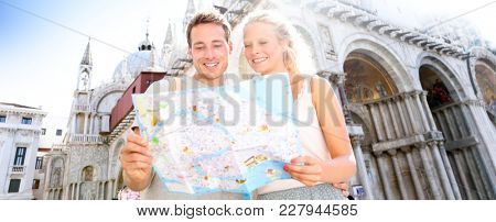Travel banner, couple reading map in Venice, Italy on Piazza San Marco by Saint Mark's Basilica. Happy young couple on travel vacation in Europe. Happy woman and man in love traveling together.