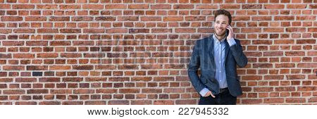 Business man talking on mobile phone panoramic banner of brick wall background texture. Happy young businessman using cellphone in urban setting wearing smart casual suit.
