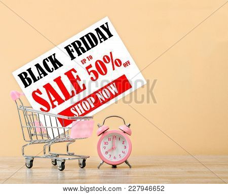Black Friday Sale Card In Shopping Cart And Pink Alarm Clock On Wooden Background. Business Concept.
