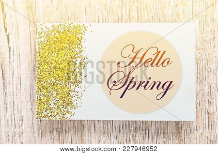 Hello Spring Card With Gold Glitter On Wooden Background.