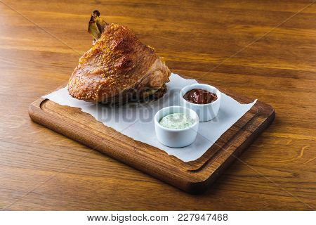 Close-up View Of Gourmet Roasted Pork Knuckle With Sauces On Wooden Tabletop