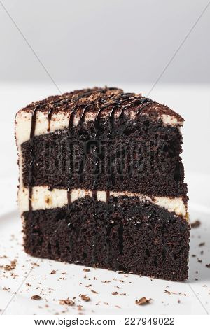 Closeup View Of Chocolate Cake With Glaze On White Plate