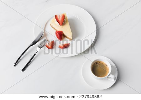 Coffee Cup With Strawberry Cheesecake On Plate And Cutlery