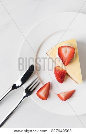 Top View Of Cheesecake With Strawberries And Cutlery On White