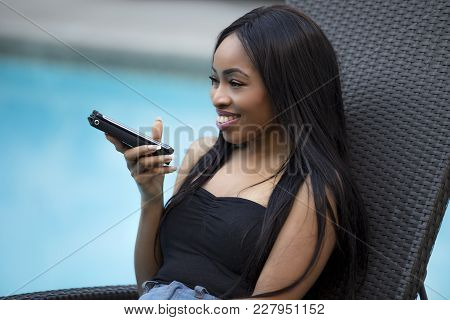 Black female on a speaker phone call in a hotel resort.  She is working while on vacation or dictati