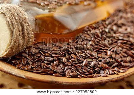 Linseed Oil In A Glass Bottle In The Clay Ceramic Plate Full Of Raw Flax Seeds On A Brown Rustic Woo