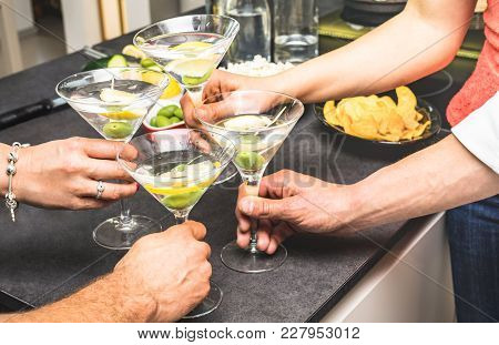 Hands Of Friends Having Fun At House Party With Pre Dinner Aperitif Martini Cocktails And Chips Oliv
