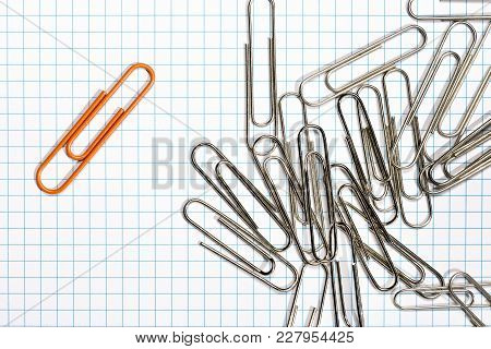 Orange Paper Clip With Silver Paper Clips On A Grilled Background