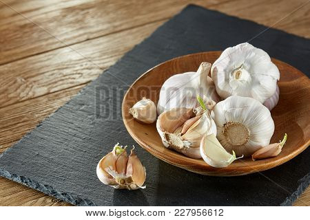 Garlic On Flat Wooden Plate Put On Black Piece Of Board On Rustic Wooden Background. Close-up, Shall