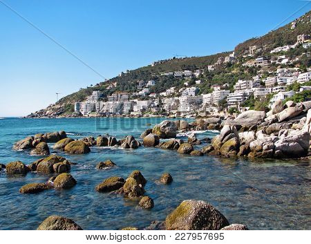 Boulders Lying All Around The Fore Ground In The Tranquil Blue Water With A Mountain Covered In Vege