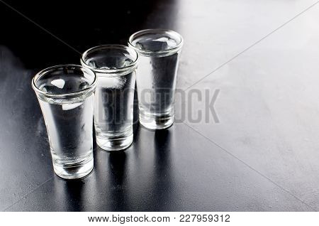 Three Vodka Shots With Ice On Black Table, Copy Space