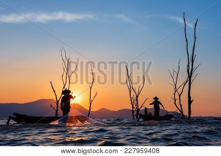 Fisherman On Wooden Boat Casting A Net For Catching Freshwater Fish In Reservoir At Sunrise.