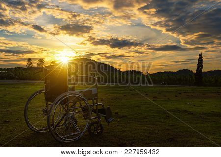 Empty Wheelchair On The Meadow At Sunset.helping And Support Concept.
