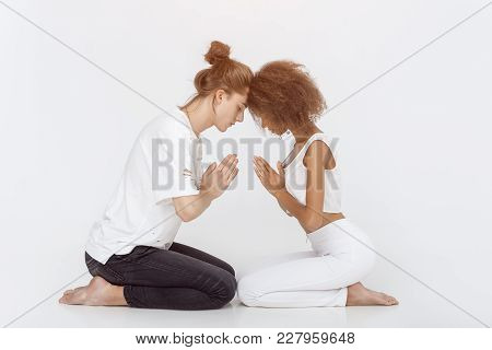 Young Mixed-race Couple Practicing Yoga Indoors On White Background. Young Afro-american Woman And C