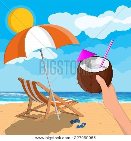 Coconut With Cold Drink In Hand. Landscape Of Wooden Chaise Lounge, Umbrella, Flip Flops On Beach. S