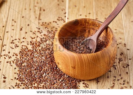 Top View Close-up Picture Of Flax Seeds In Wooden Bowl And Spoon Isolated On Brown Rustic Wooden Bac