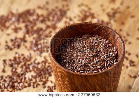 A Wooden Bowl With Linseeds On A Brown Rustic Wooden Background Seen From The Opening, Close-up, Sha