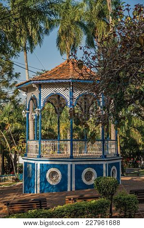 Close-up Of An Old Colorful Gazebo In The Middle Of Verdant Garden Full Of Trees, In A Sunny Day At
