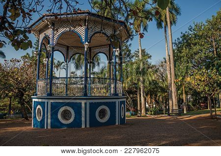 Old Colorful Gazebo Of Square In The Middle Of Verdant Garden Full Of Trees, At Sunset In São Manuel